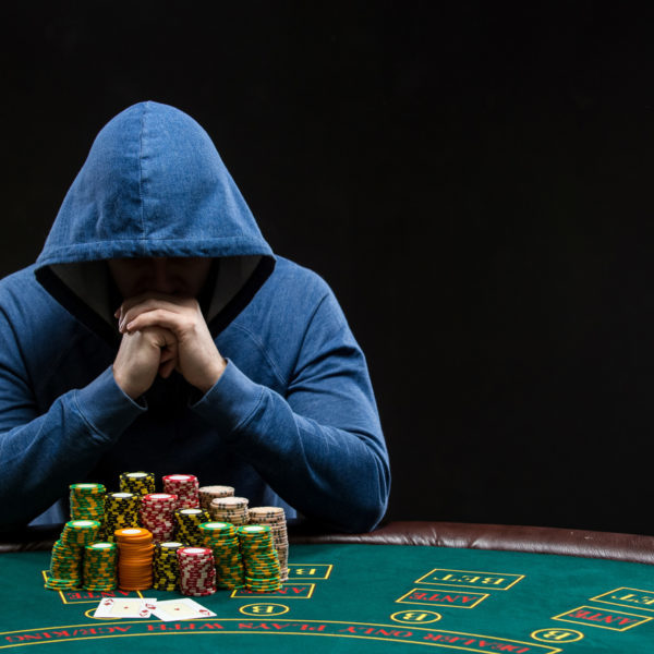 Poker player sitting at a poker table with chips table trying to hide his expressions and looking at combination of two aces. Closeup